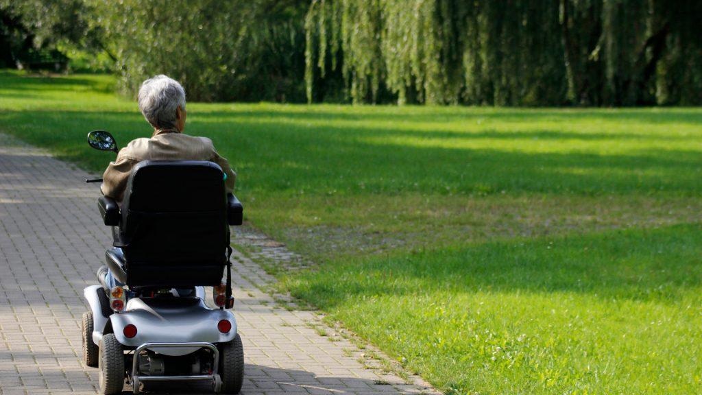 Man in wheelchair drives through park